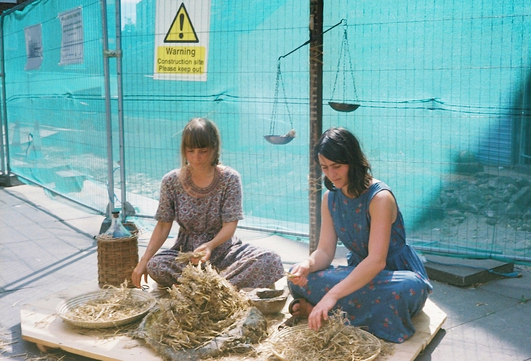 Two people making bundles of straw