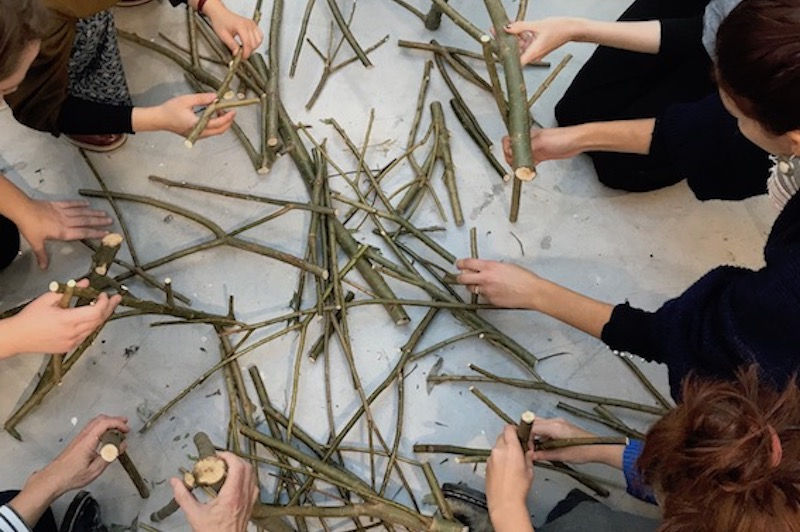 a group of people handling some sticks