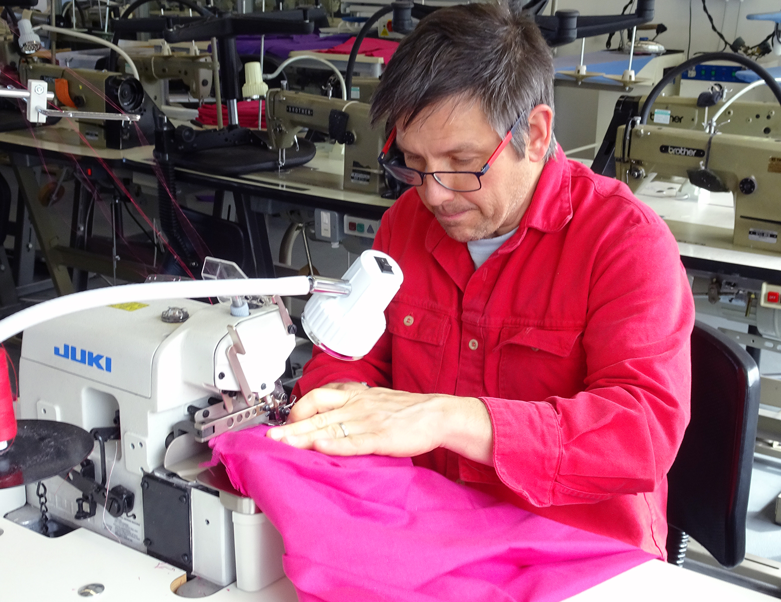 Man using overlocker sewing machine