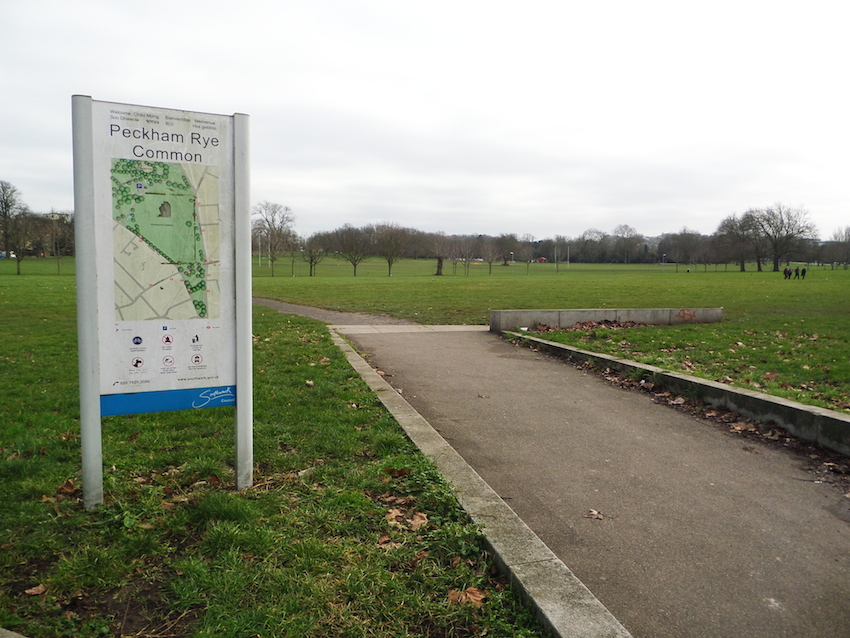 Large green open space with path and sign