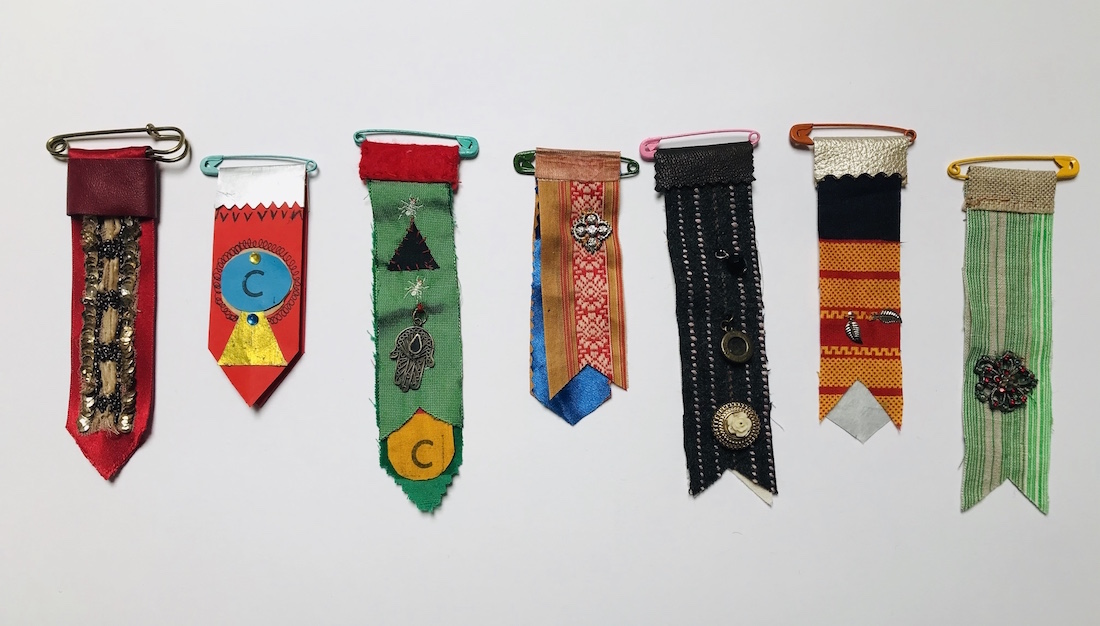 colourful strips of textiles attached to large safety pins to create impromptu 'medals'