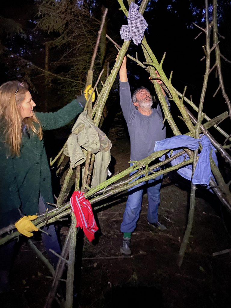 two people building a structure with alder poles