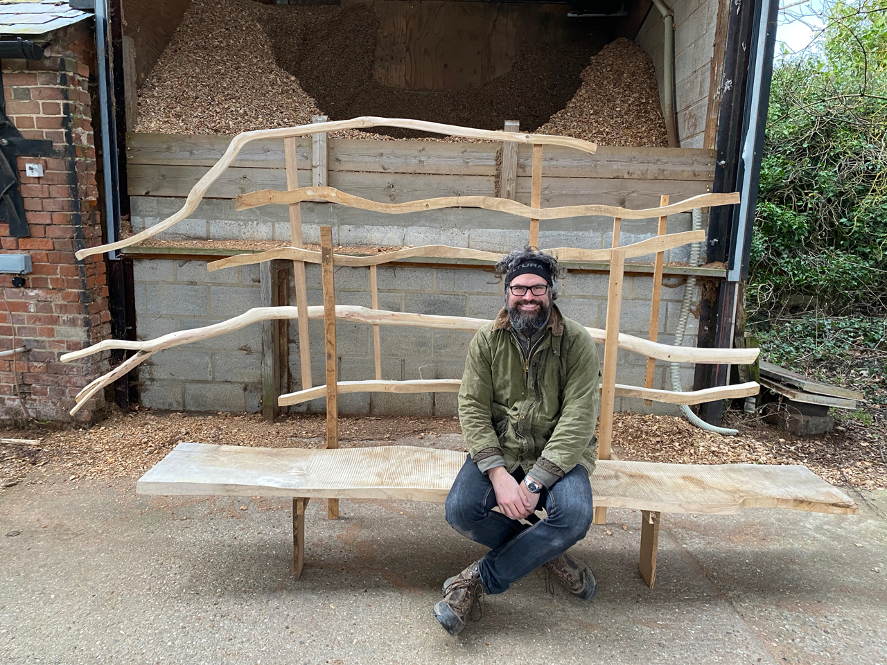 a man sitting on a large bench made from green wood